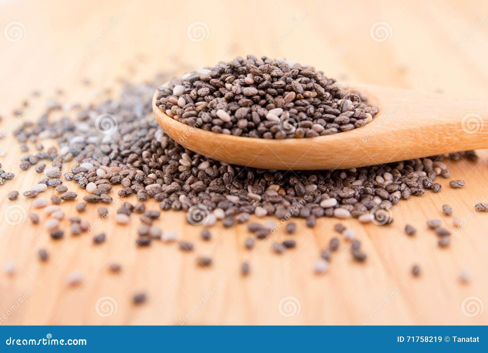 Κλείστε επάνω των σπόρων Chia σε ένα ξύλινο κουτάλι στον πίνακα