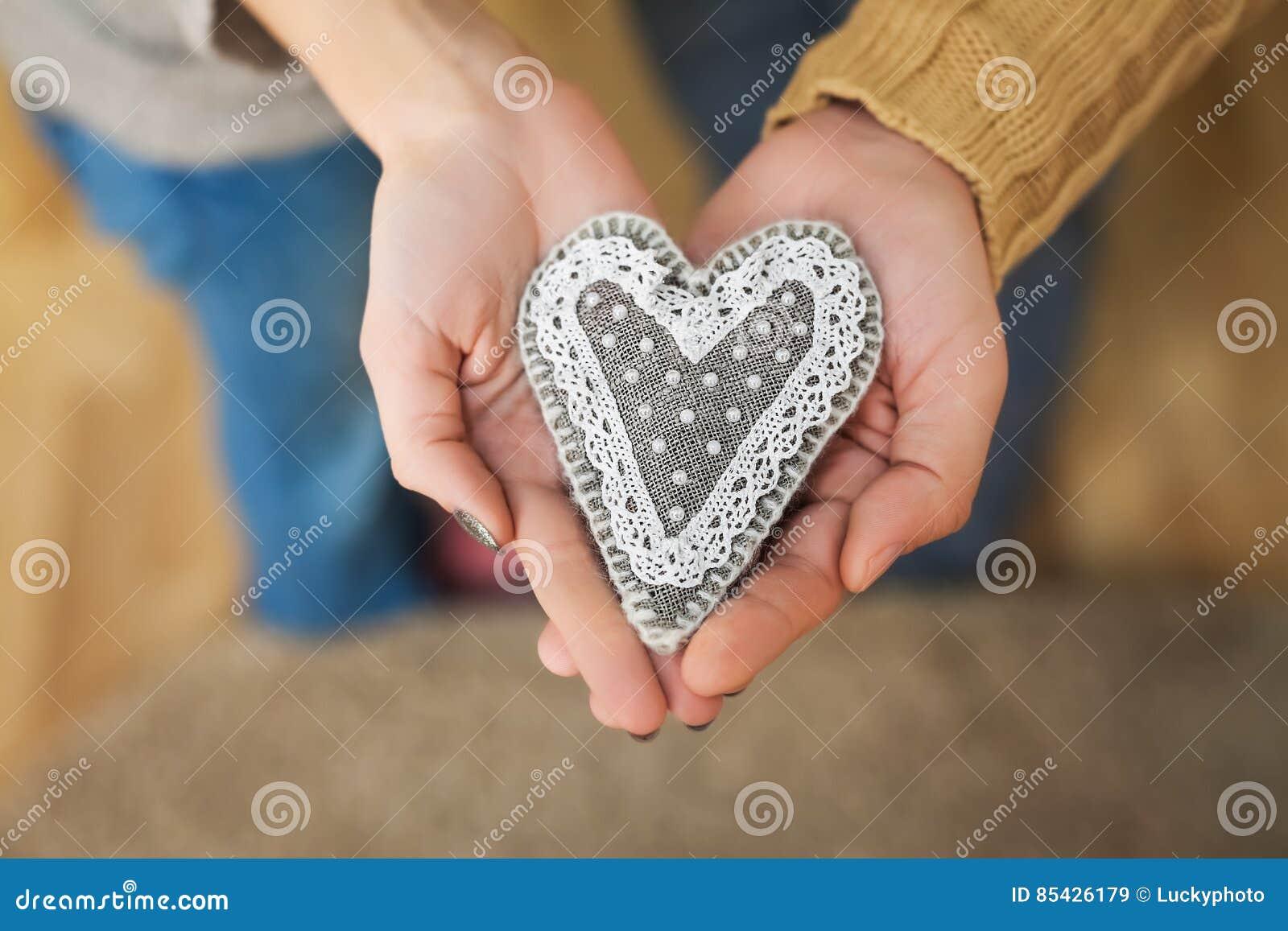 Κλείστε επάνω των χεριών γυναικών και ανδρών με την καρδιά