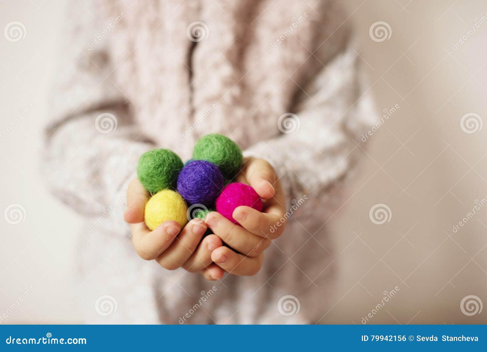 Κλείστε επάνω των χεριών παιδιών κρατώντας τις ζωηρόχρωμες αισθητές σφαίρες Παιδί, φοίνικες παιδιών Ένα μικρό κορίτσι κρατά στις