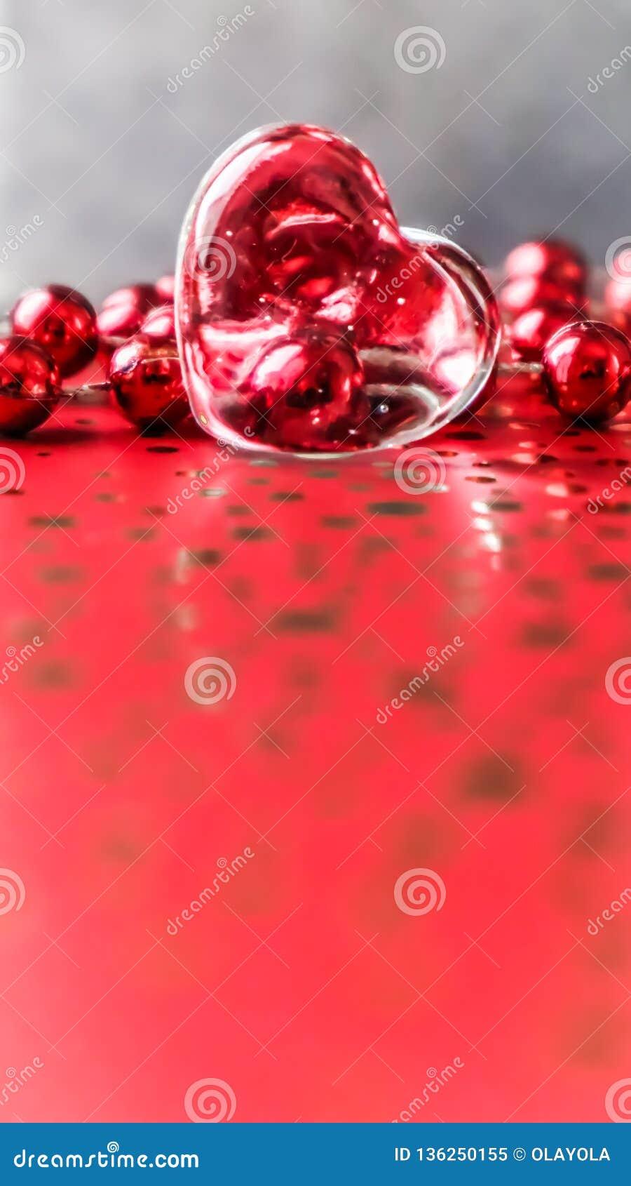 Λάμποντας διαφανής καρδιά και μια ομάδα κόκκινων χαντρών Τέλειο υπόβαθρο ευχετήριων καρτών ημέρας βαλεντίνων Κάθετη εικόνα στον κ