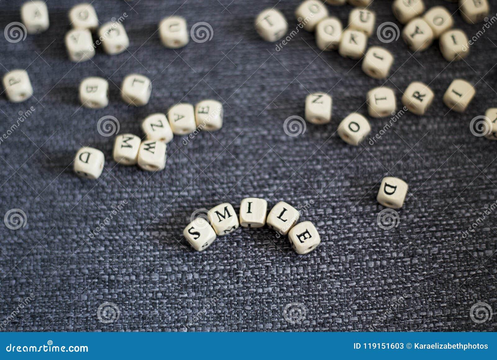 Λέξη χαμόγελου τίτλου σε ένα γκρίζο υπόβαθρο υφάσματος