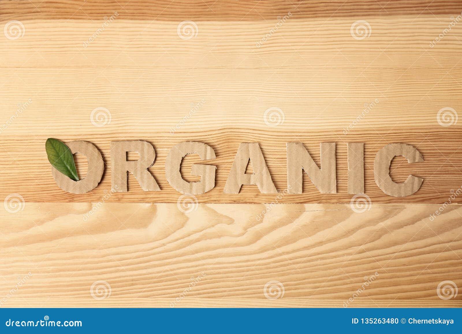 """Λέξη """"οργανικός """"φιαγμένος από επιστολές χαρτονιού και πράσινο φύλλο στο ξύλινο υπόβαθρο"""