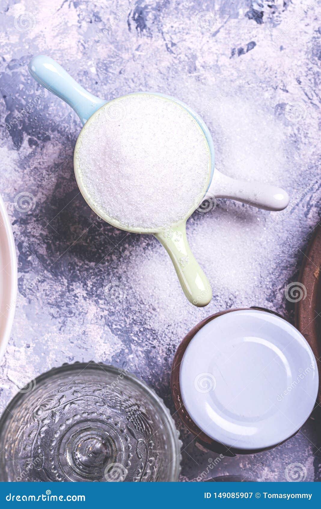 Λίγα μικρά καλύμματα που συσσωρεύονται στο γκρίζο σύνολο πινάκων της ζάχαρης