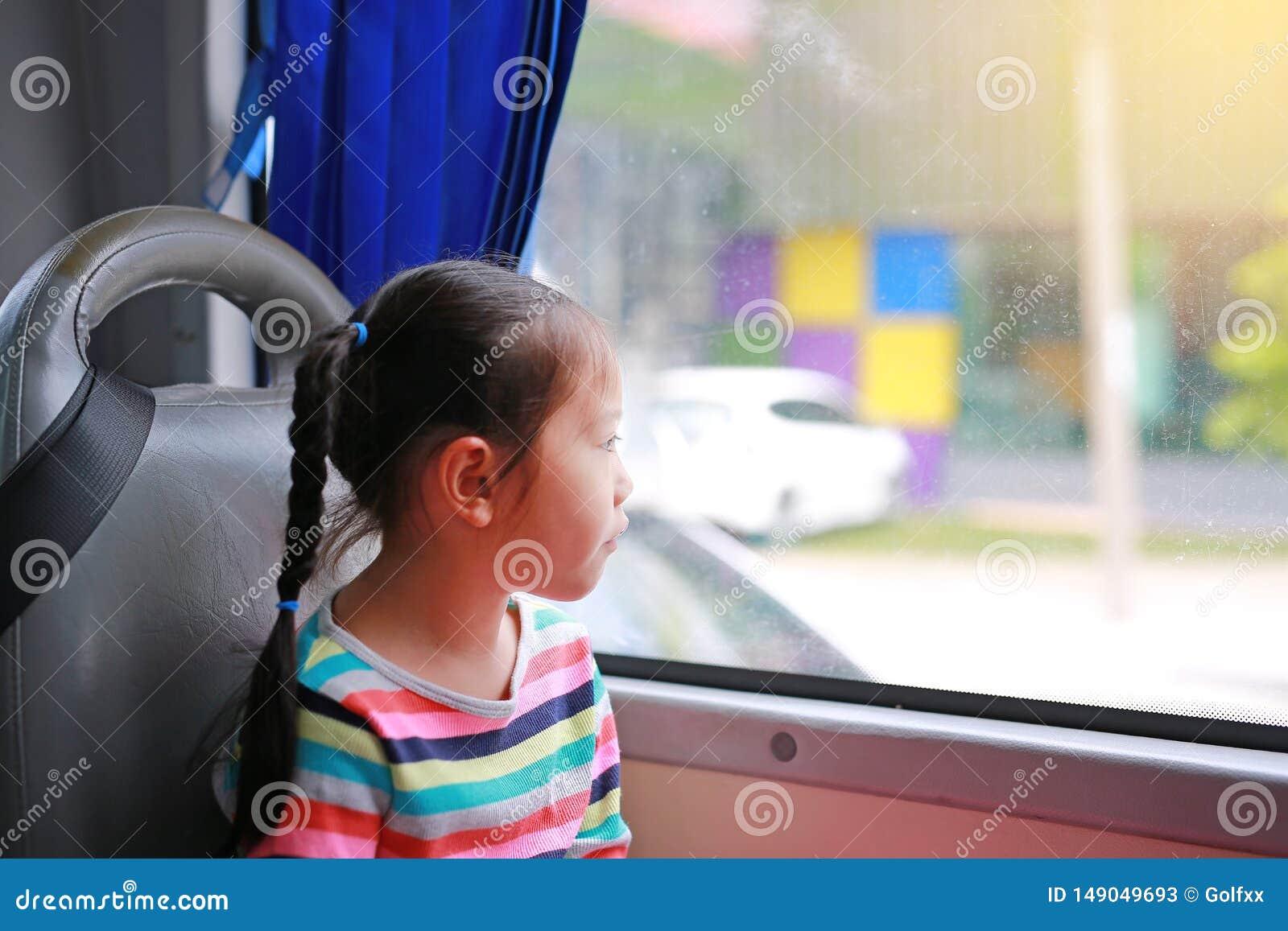 Λίγη ασιατική συνεδρίαση κοριτσιών στο λεωφορείο δημόσιων συγκοινωνιών και κοίταγμα έξω