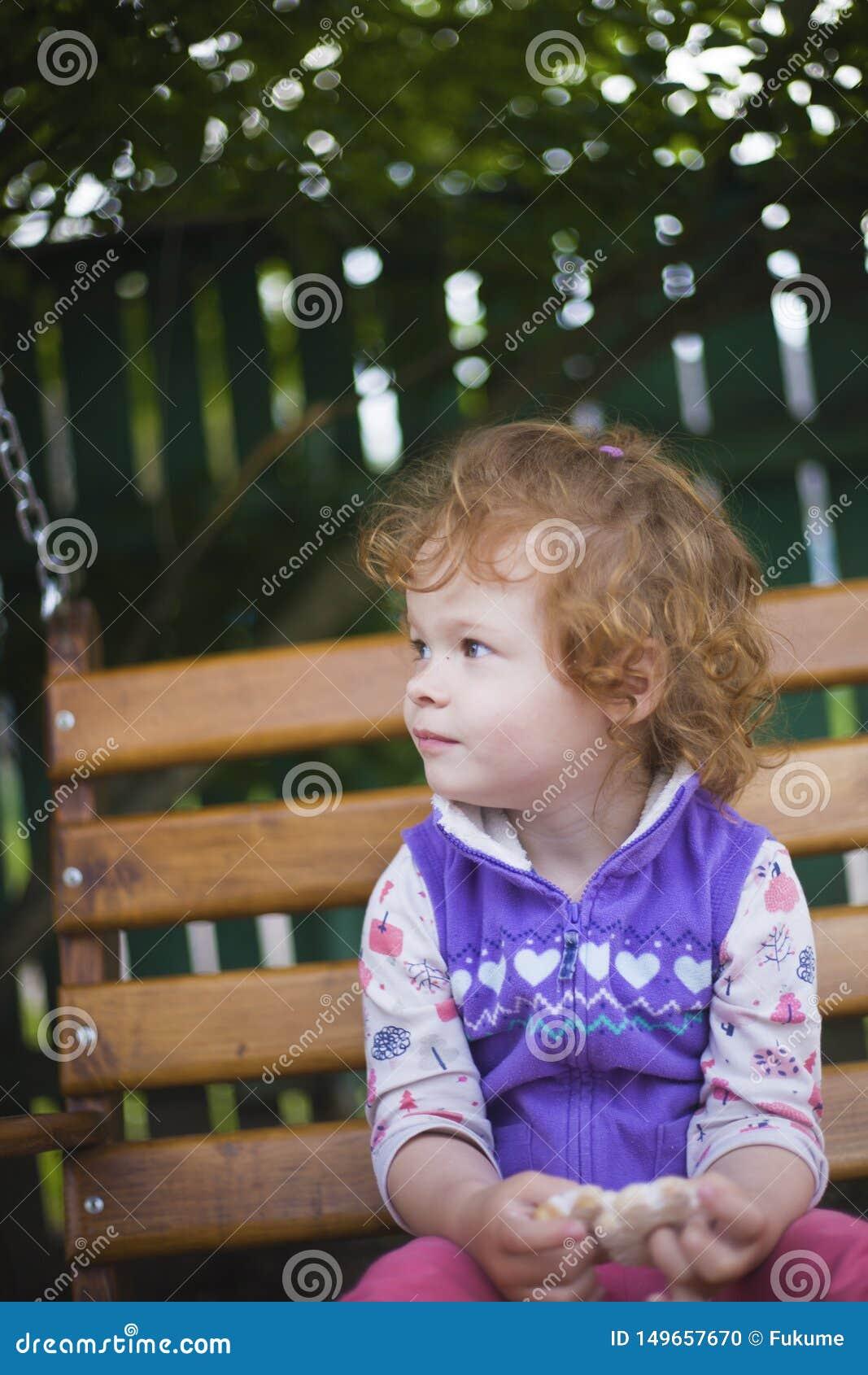 Λίγη redhead συνεδρίαση κοριτσιών σε έναν πάγκο