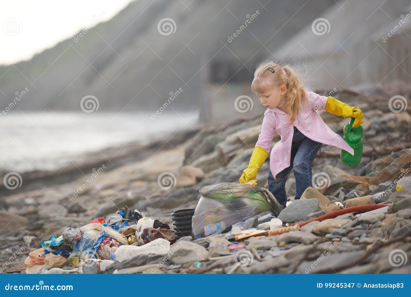 Λίγος janitor που παίρνει τα απορρίματα στην παραλία