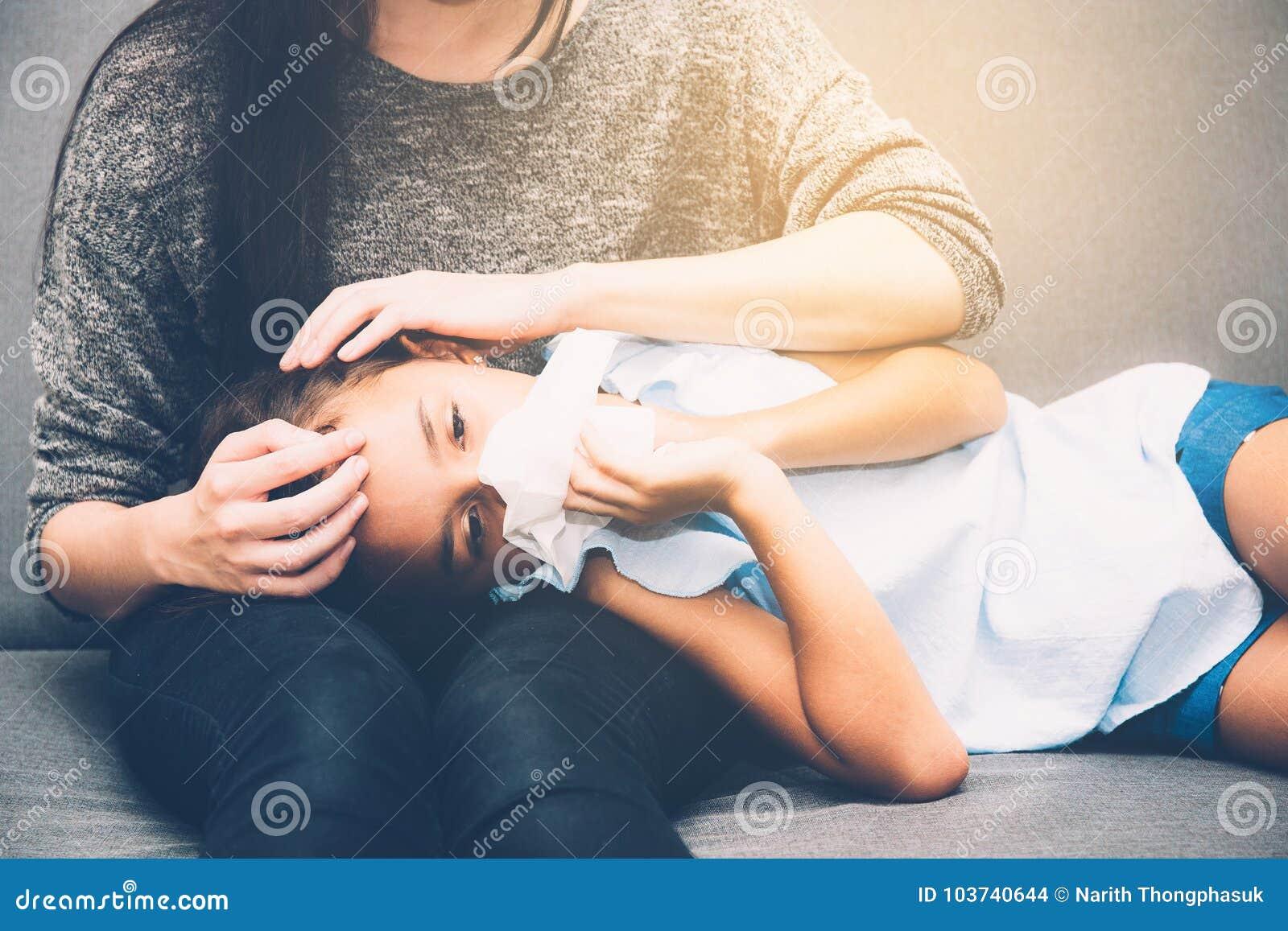Λίγο ασιατικό κορίτσι είναι άρρωστο αδύνατο να βρεθεί στον καναπέ με τη μητέρα παίρνει την προσοχή
