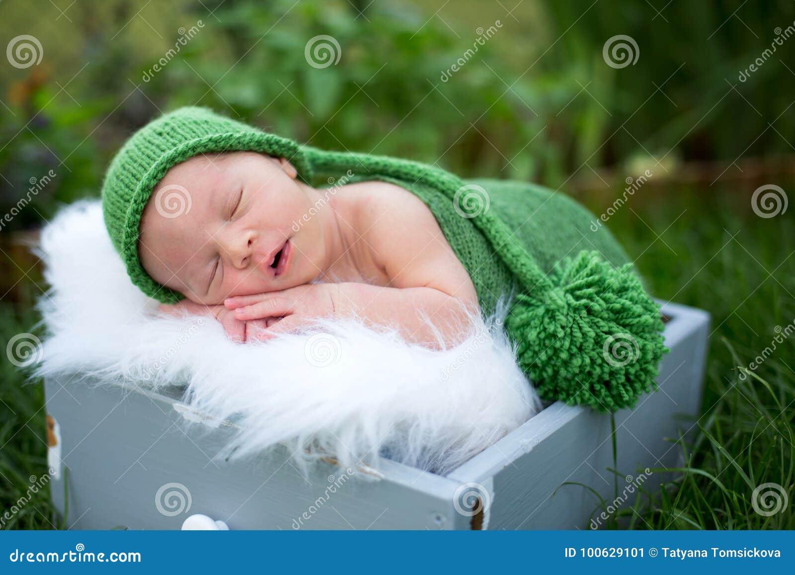 Λίγο γλυκό νεογέννητο αγοράκι, που κοιμάται στο κλουβί με το περικάλυμμα και το χ