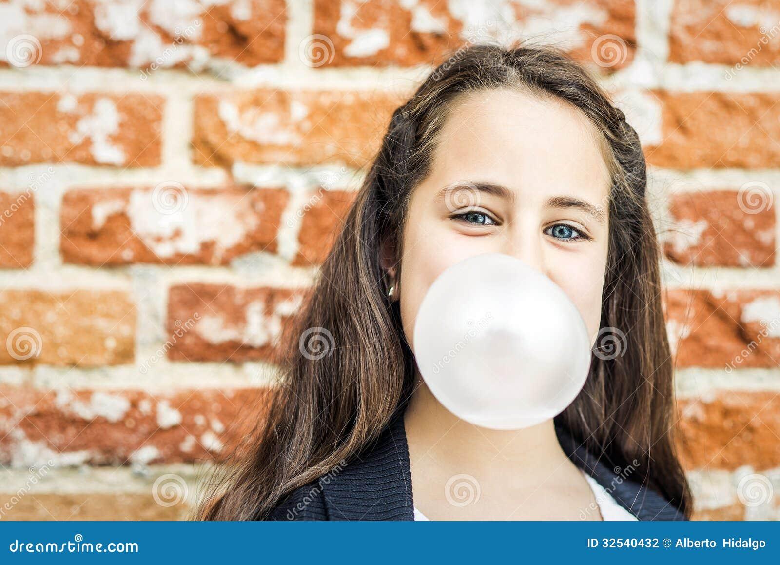 Λίγο ευτυχές κορίτσι που φυσά μια τσίχλα