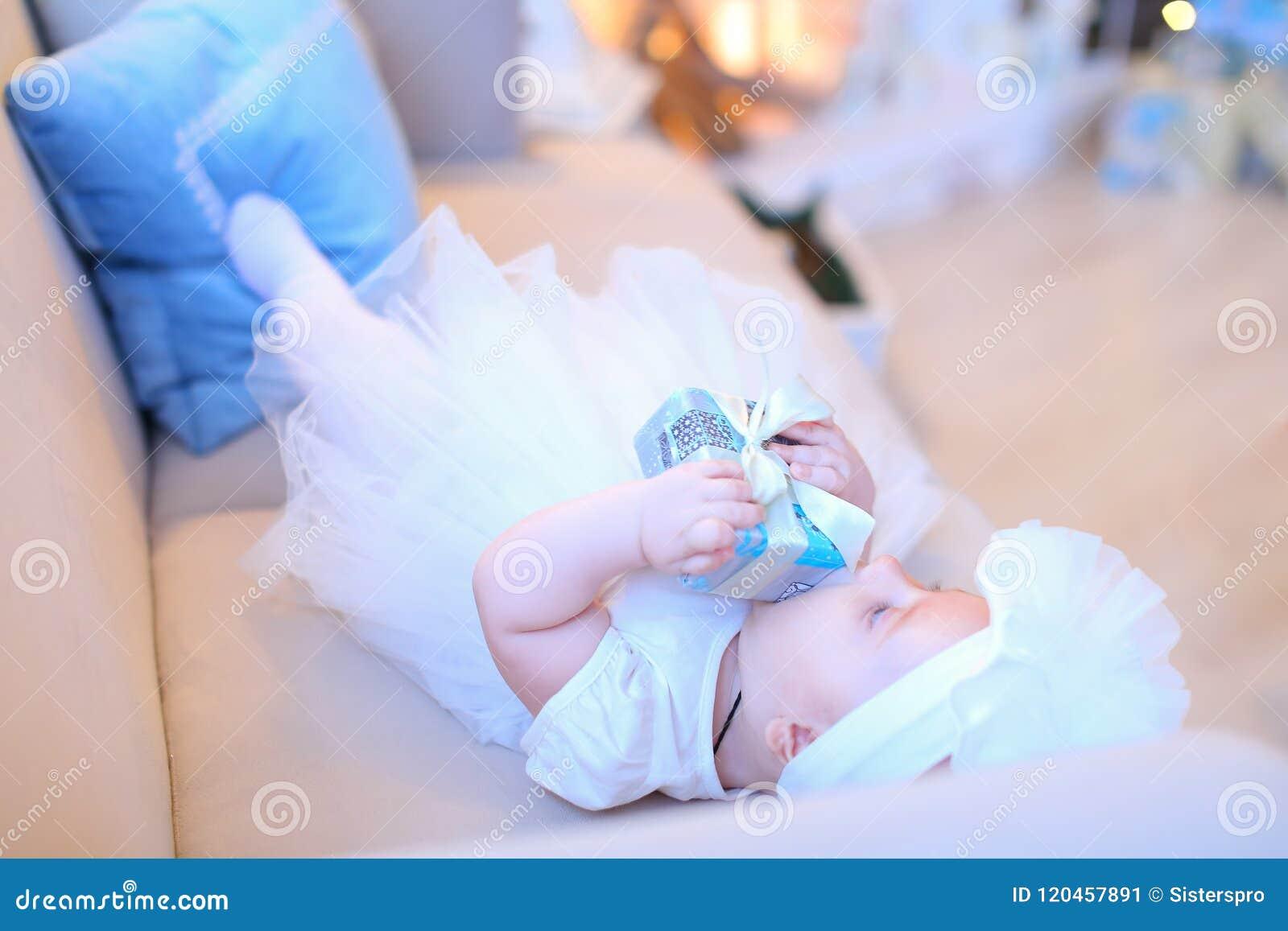 Λίγο θηλυκό μωρό που βρίσκεται στον καναπέ και που φορά τα άσπρα ενδύματα