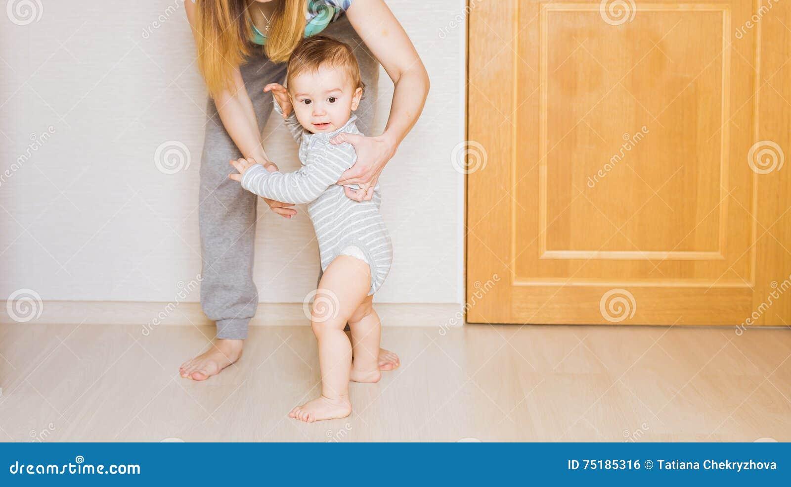 Λίγο μωρό παιδιών που χαμογελά κάνοντας τα πρώτα βήματα