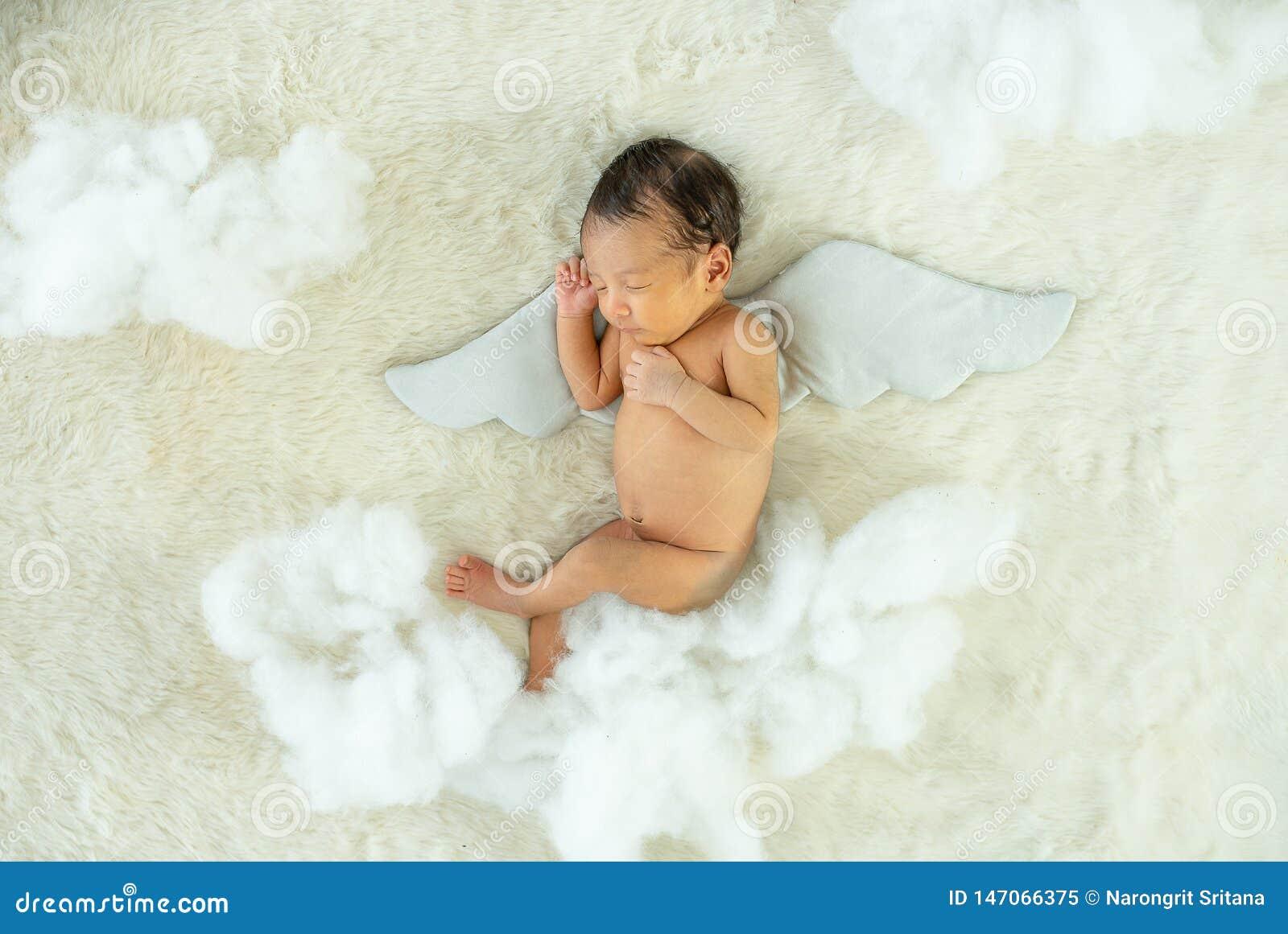 Λίγο νεογέννητο μωρό κοιμάται στο άσπρο κρεβάτι με τα βοηθητικά και χνουδωτά pandas φτερών