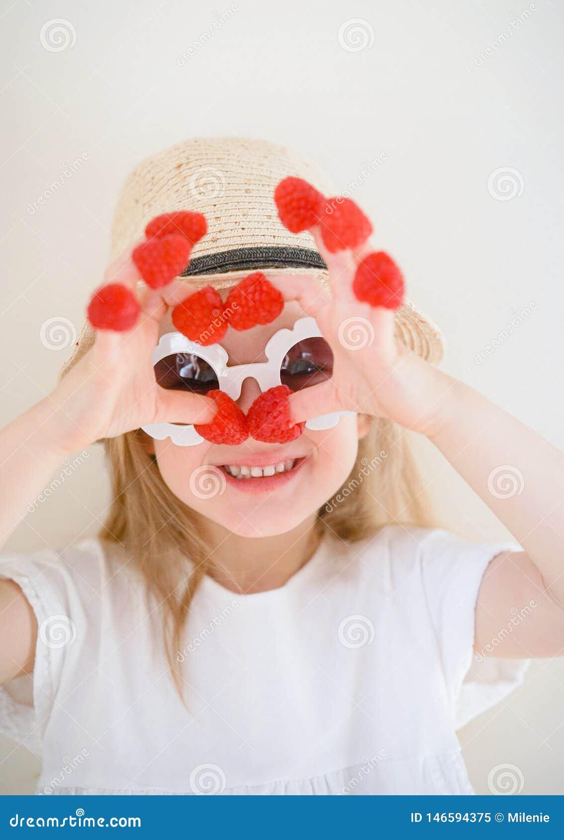 Λίγο χαριτωμένο ξανθό κορίτσι με τα σμέουρα στα δάχτυλά της, διαφορετικές συγκινήσεις, εσωτερικές