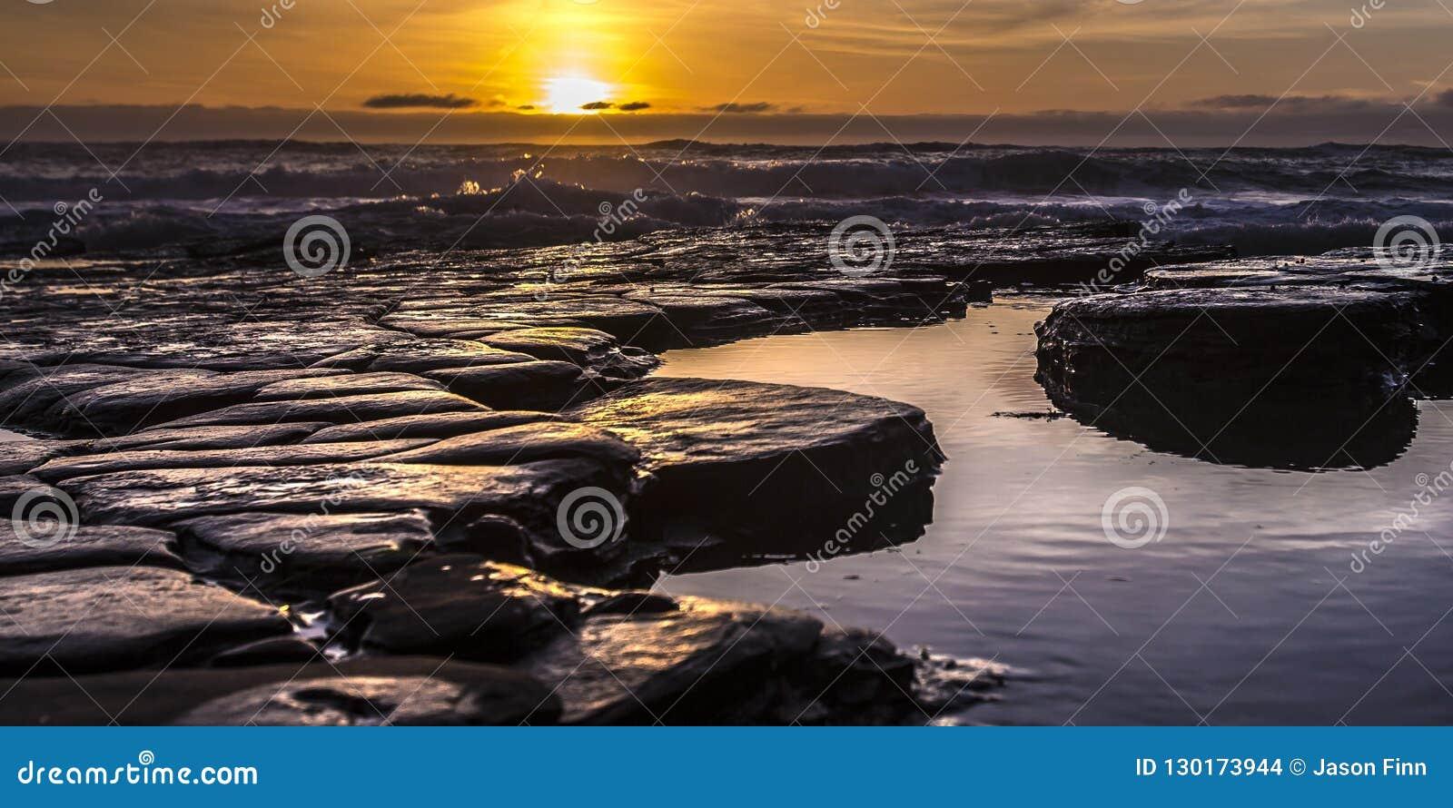 Λίμνες παλίρροιας με τον ήλιο που θέτει στον ορίζοντα