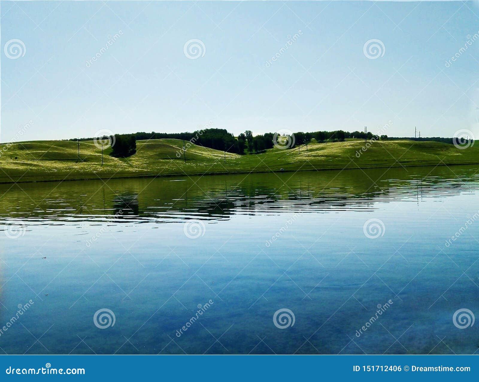 Λίμνη σε μια ήρεμη ακτή σε έναν λάμποντας οργιμένος ουρανό και ένα όμορφο τοπίο