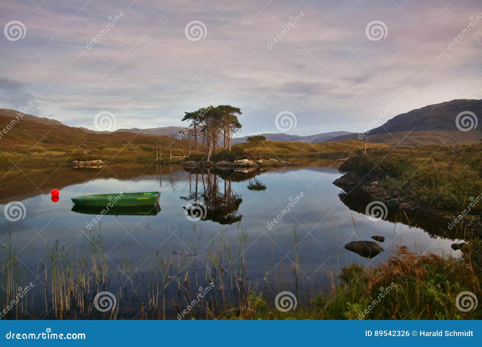 Λίμνη Assynt στο ηλιοβασίλεμα με τη βάρκα, δέντρα, βουνά, αντανακλάσεις στο νερό