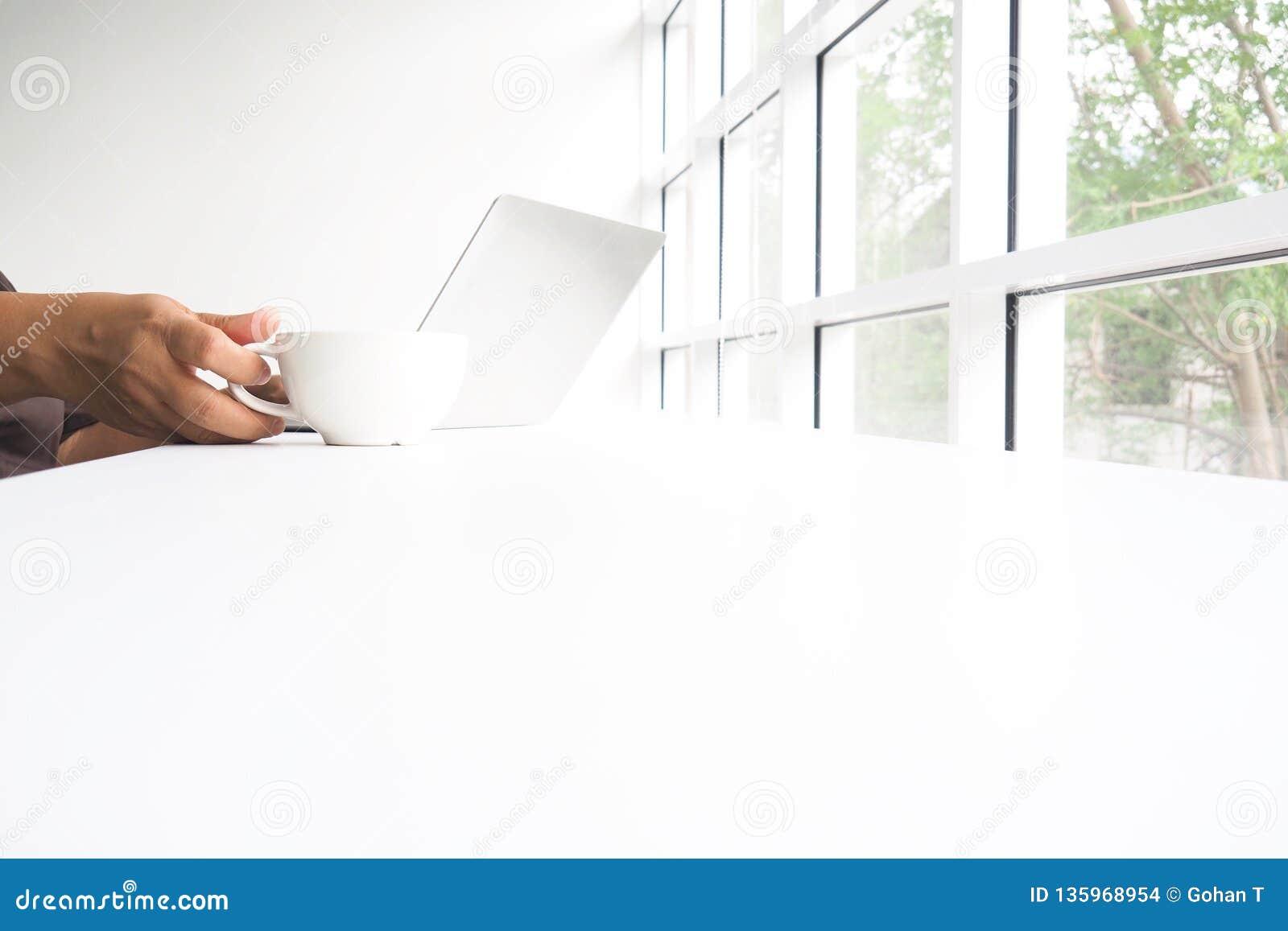 Λαβή φλυτζανιών καφέ και άσπρο σημειωματάριο για την εργασία εκτός από το παράθυρο