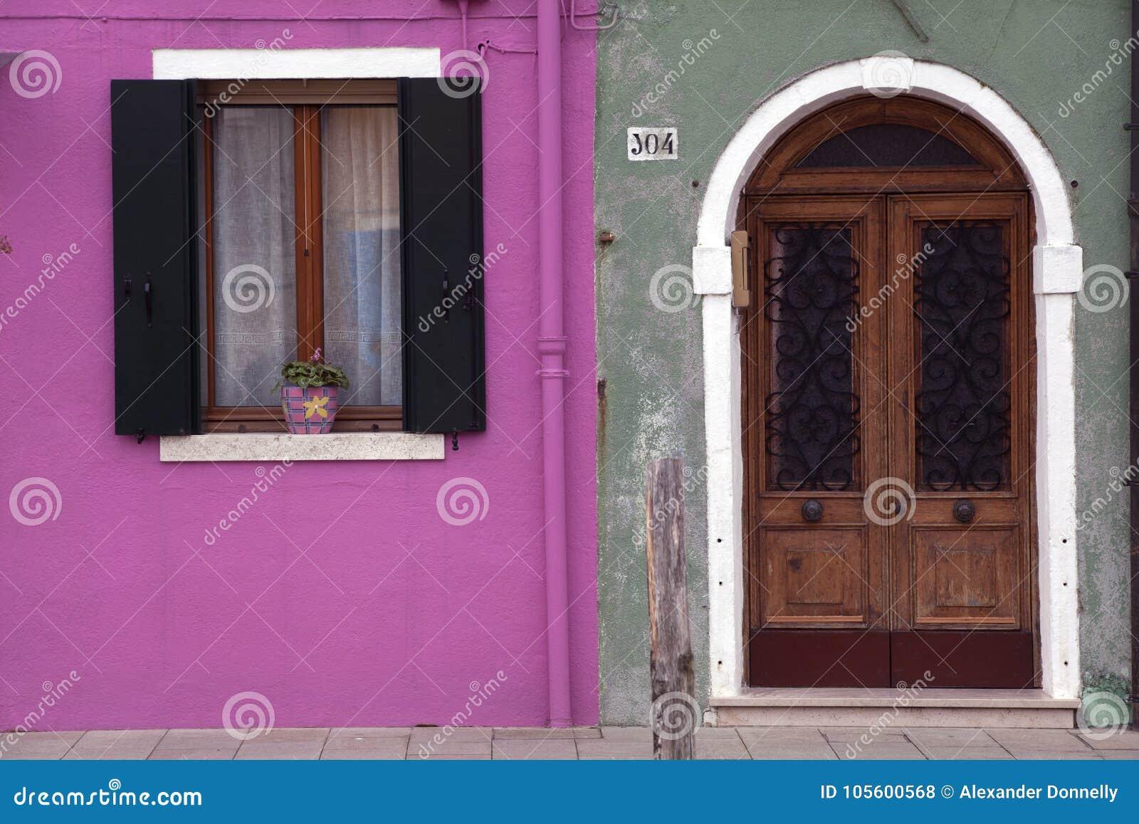Λαμπρά χρωματισμένες ρόδινες και πράσινες παραθυρόφυλλα παραθύρων τοίχων και πόρτα Burano Βενετία αψίδων
