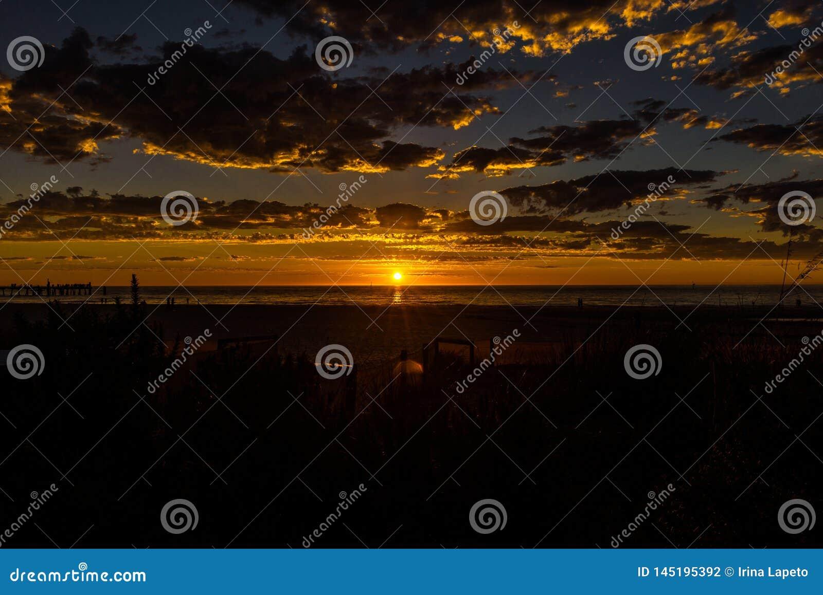 Λαμπρό seascape ηλιοβασιλέματος στην παραλία Glenelg, Αδελαΐδα, Αυστραλία