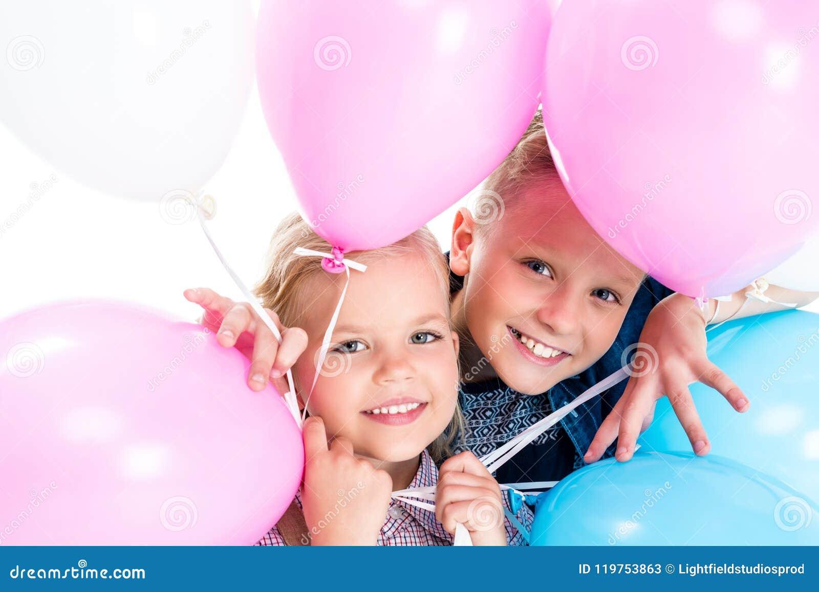 λατρευτοί ευτυχείς αμφιθαλείς που κρατούν τα μπαλόνια και που χαμογελούν στη κάμερα