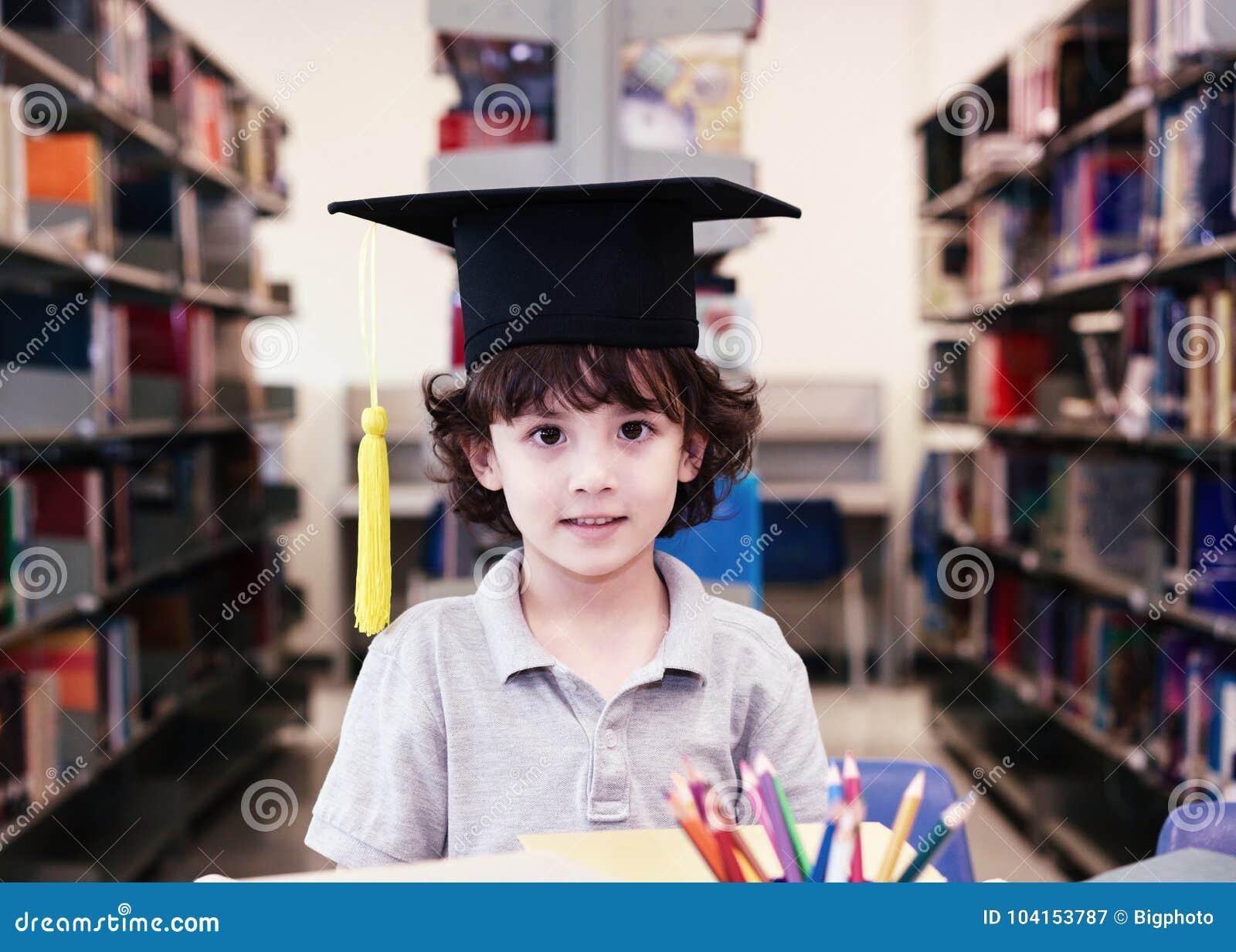 Λατρευτός λίγο παιδί, αγόρι, που κάθεται σε μια βιβλιοθήκη, που διαβάζει τα βιβλία