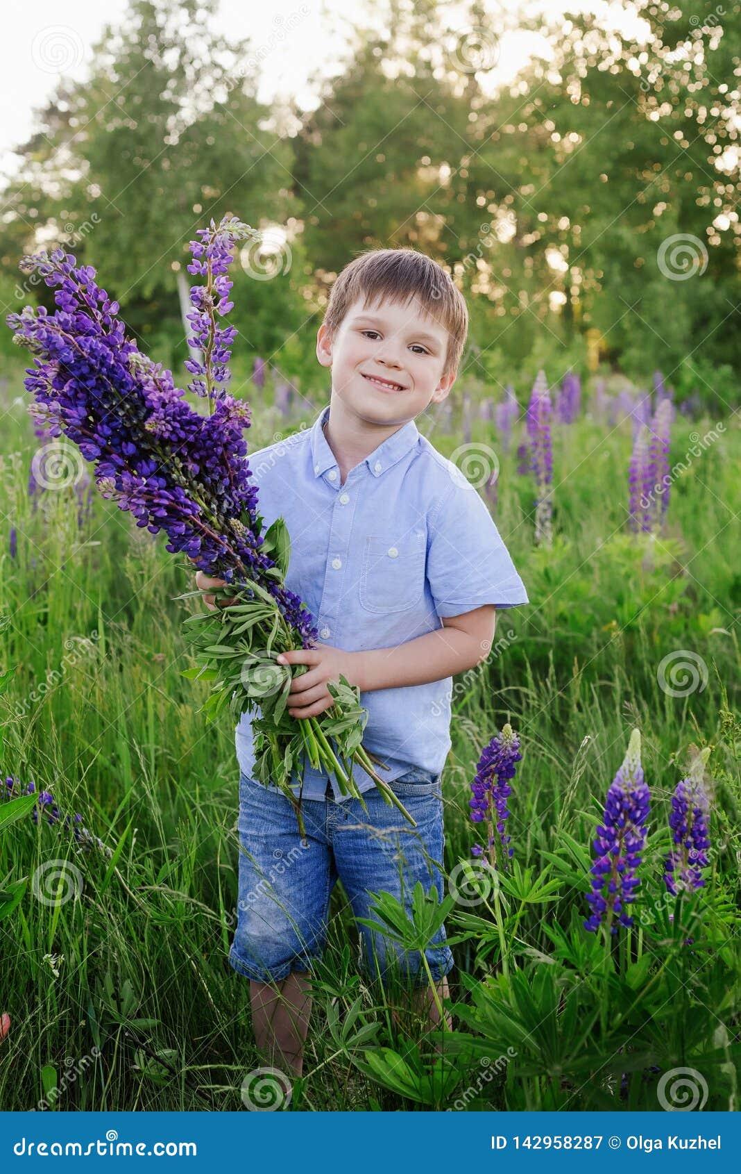 Λατρευτό αγόρι σε μια μπλε μπλούζα με μια ανθοδέσμη των λούπινων σε ένα λιβάδι