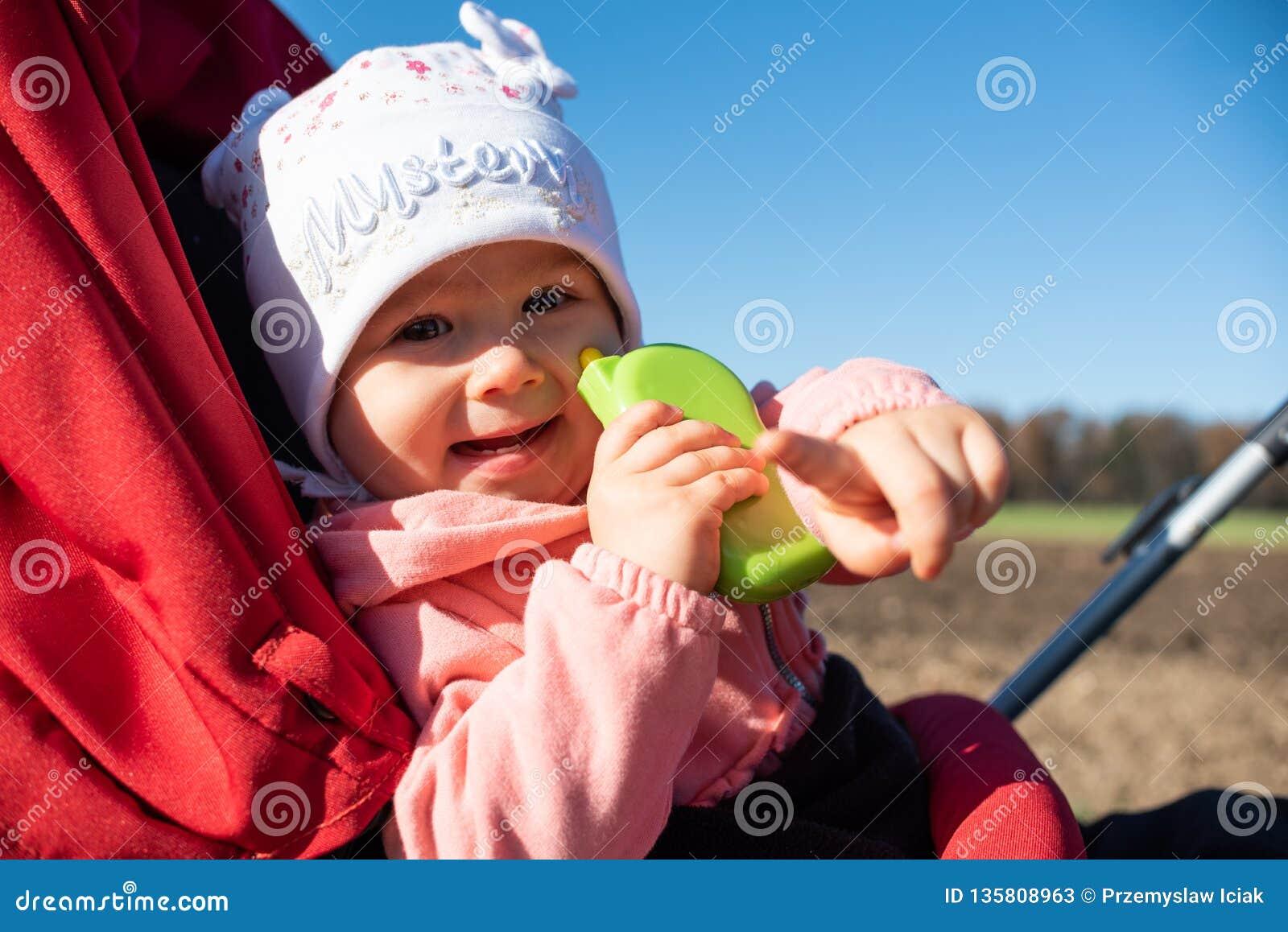 Λατρευτό κοριτσάκι έξω στον κόκκινο περιπατητή στους πράσινους τομείς σε έναν δρόμο, ηλιόλουστη ημέρα Μωρό με το πράσινο παιχνίδι