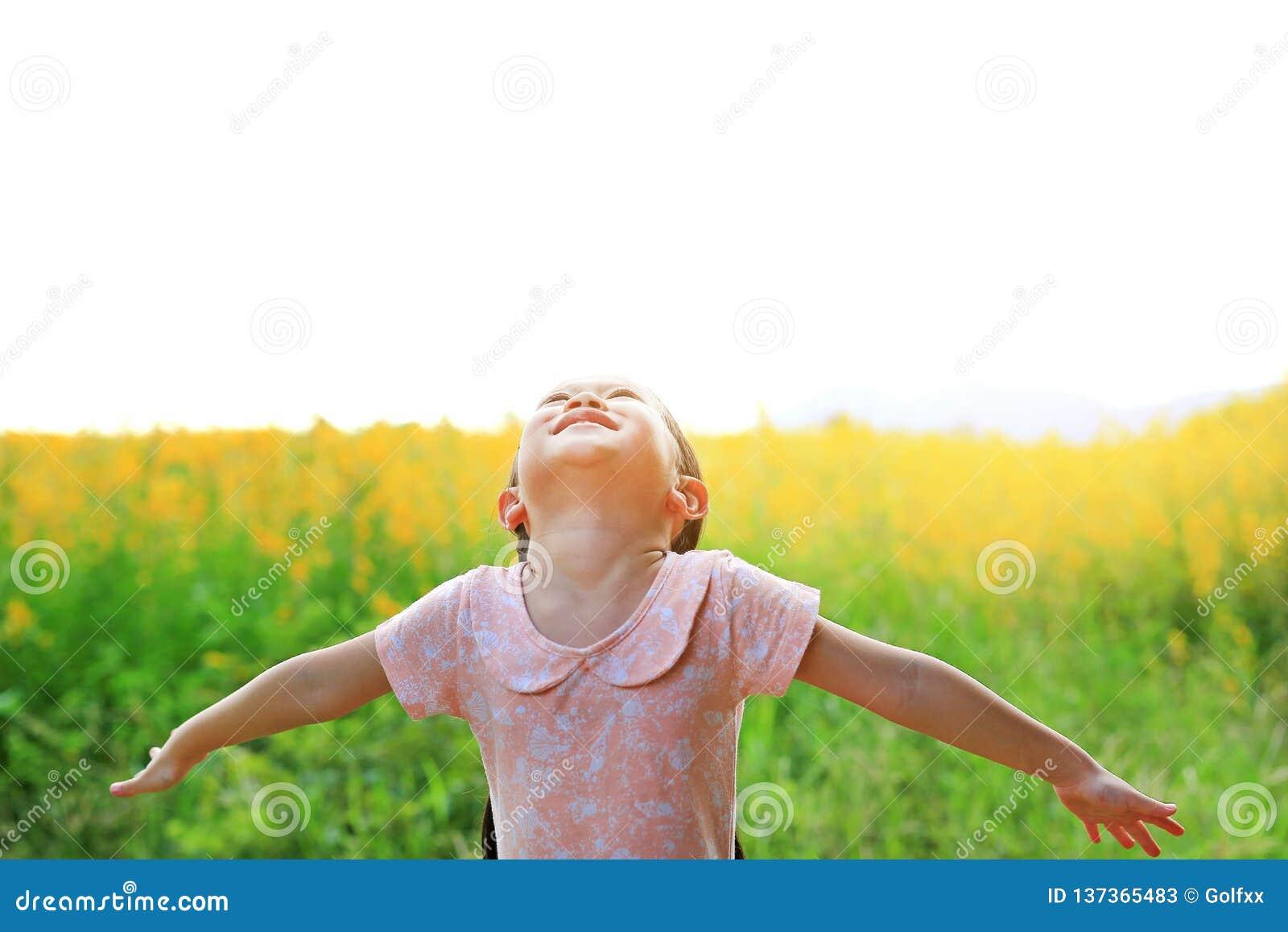 Λατρευτό λίγο ασιατικό κορίτσι παιδιών που αισθάνεται ελεύθερο με χαλαρώνει τις αγκάλες ευρέως ανοικτές Sunhemp στον τομέα με τα