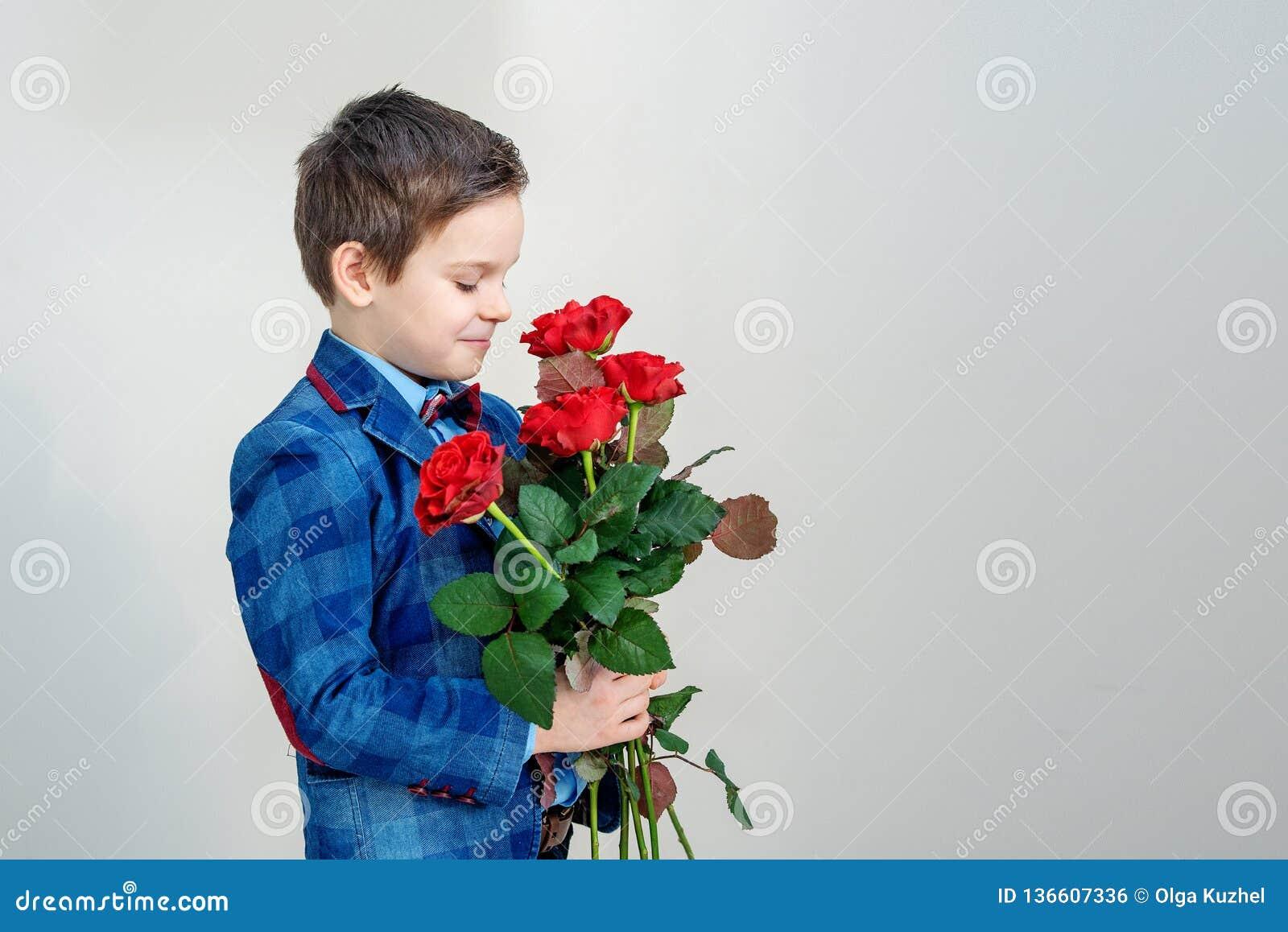Λατρευτό μικρό παιδί στο κοστούμι με την ανθοδέσμη των κόκκινων τριαντάφυλλων σε ένα ελαφρύ υπόβαθρο