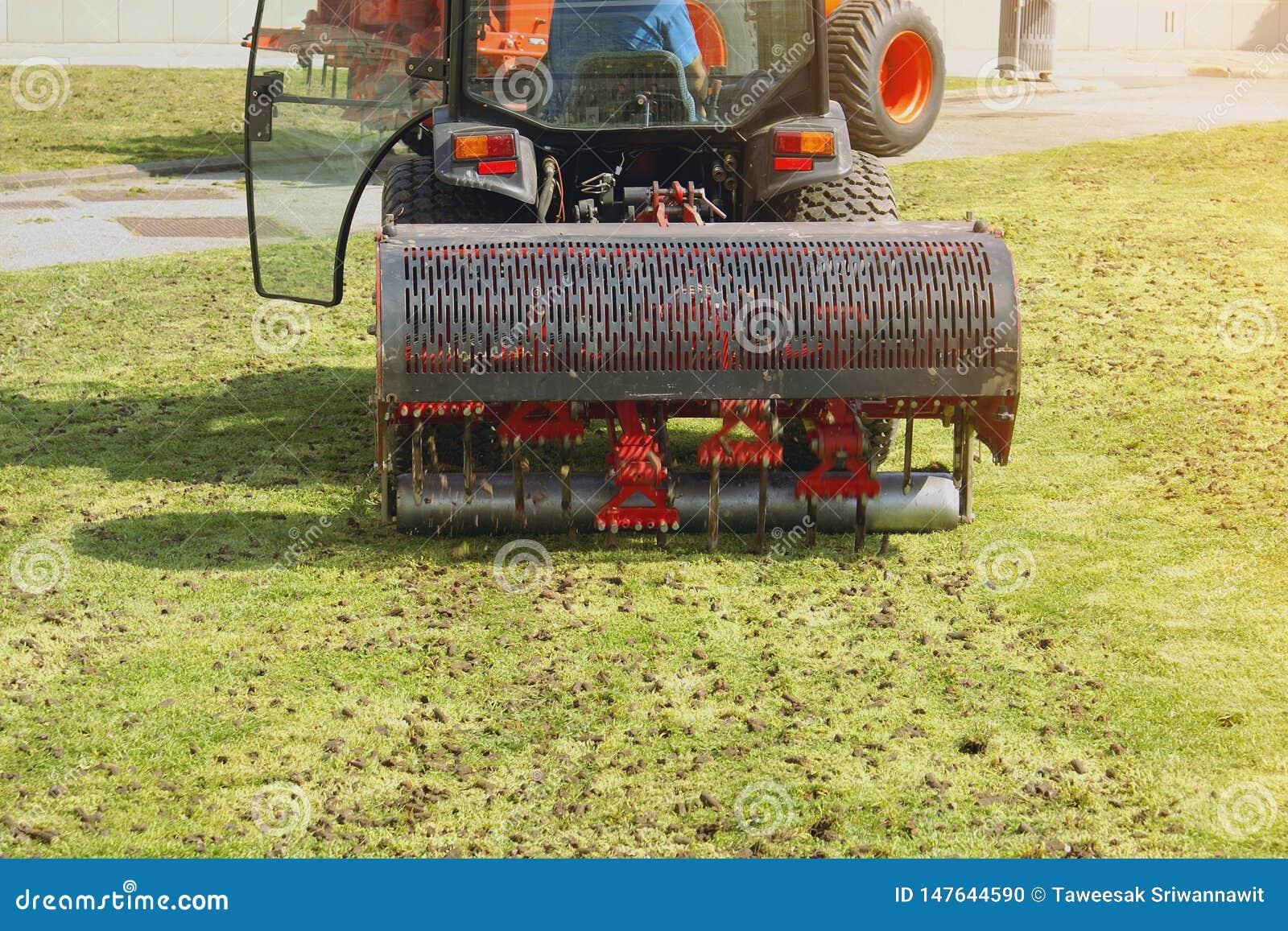 Λειτουργούσα μηχανή εδαφολογικού αερισμού κηπουρών στο χορτοτάπητα χλόης