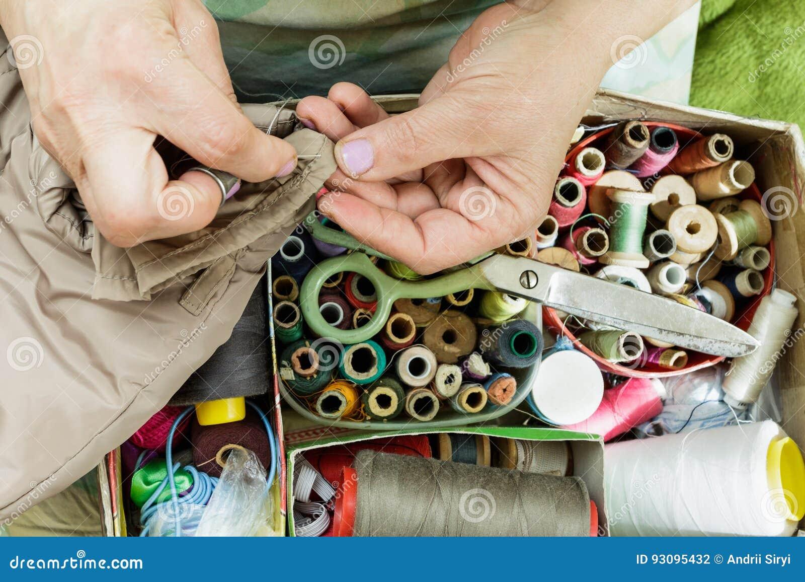 Λειτουργώντας χέρια seamstress με μια βελόνα, νήμα ψαλιδιού