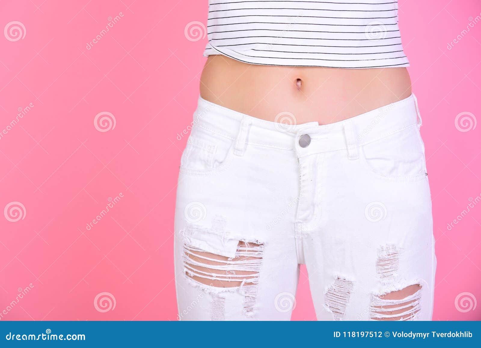 Λεπτή κοιλιά της γυναίκας στα άσπρα τζιν στο ρόδινο υπόβαθρο, διάστημα αντιγράφων να κάνει δίαιτα και ικανότητας η έννοια παρουσι