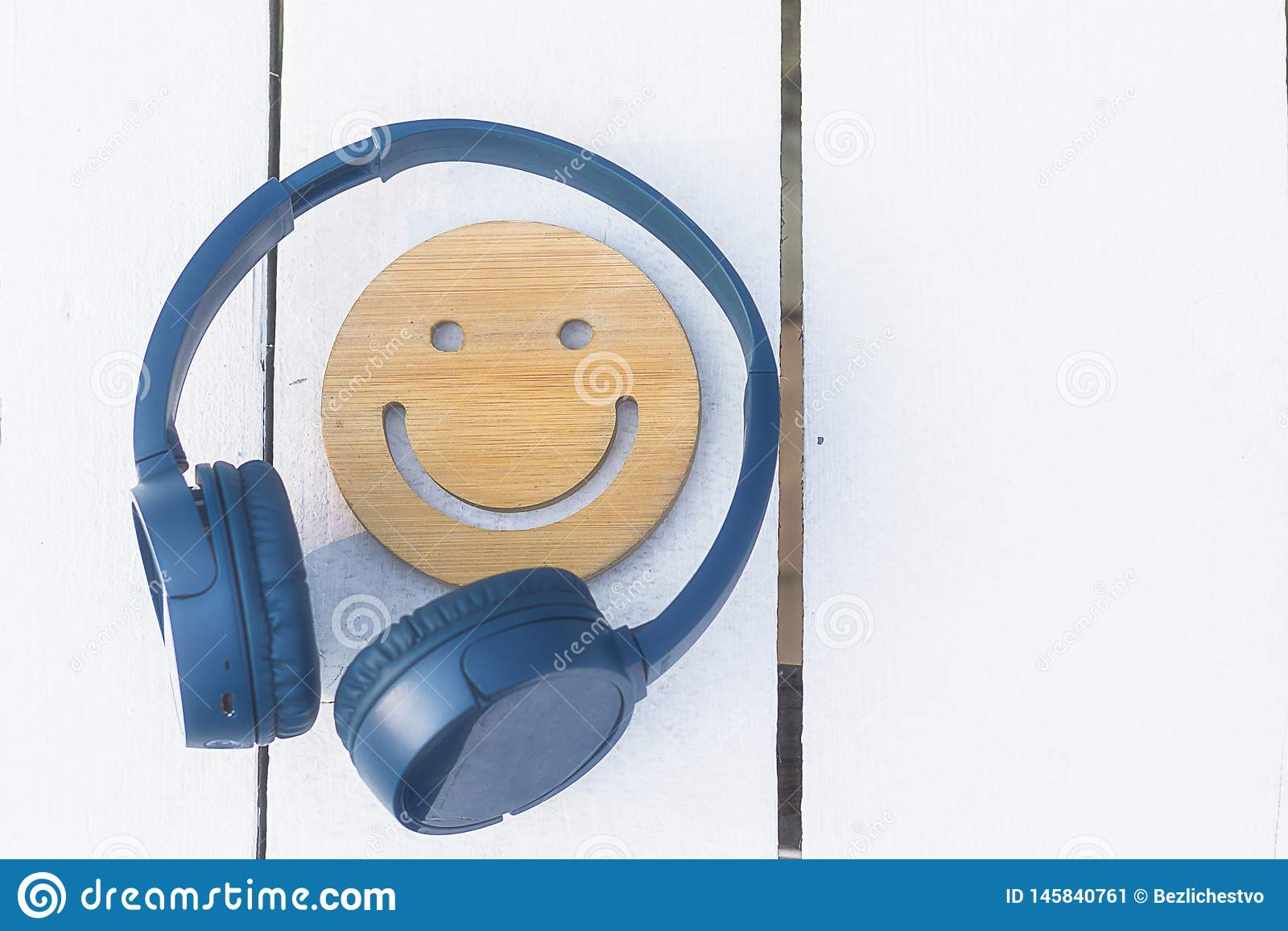 Λεπτή μουσική για την τέλεια διάθεση Τα ασύρματα ακουστικά του μπλε χρώματος βρίσκονται σε ένα άσπρο υπόβαθρο r