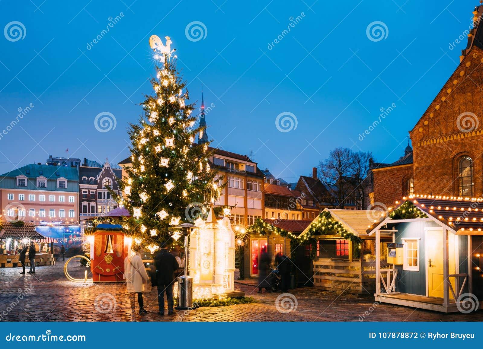 Λετονία Ρήγα Αγορά Χριστουγέννων στο τετράγωνο θόλων Χριστουγεννιάτικο δέντρο και εμπορικοί οίκοι