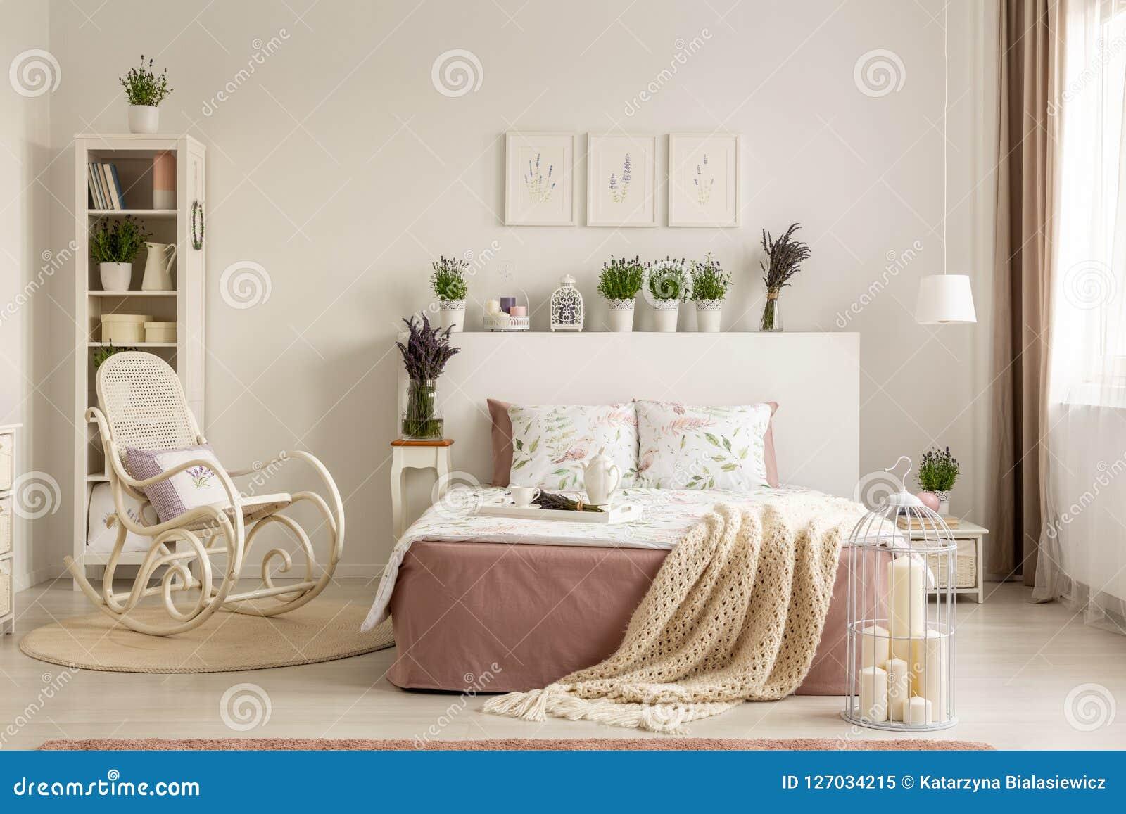 Λικνίζοντας καρέκλα δίπλα στο κρεβάτι με το κάλυμμα στο provencal εσωτερικό κρεβατοκάμαρων με τις εγκαταστάσεις και τις αφίσες Πρ