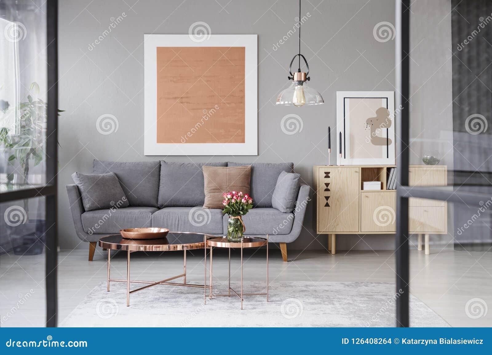 Λουλούδια στον πίνακα χαλκού μπροστά από τον γκρίζο καναπέ στο εσωτερικό καθιστικών με τη ροδαλή χρυσή αφίσα Πραγματική φωτογραφί
