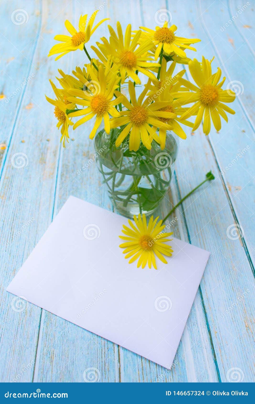 Λουλούδια Chamomile σε ένα βάζο και έναν φάκελο στον πίνακα κάρτα, μήνυμα, πρόσκληση