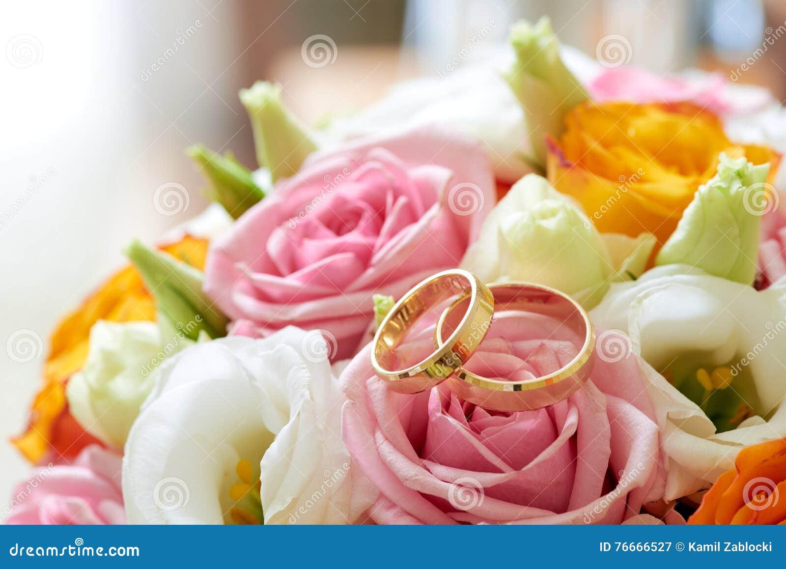 Λουλούδια ανθοδεσμών και γαμήλια δαχτυλίδια