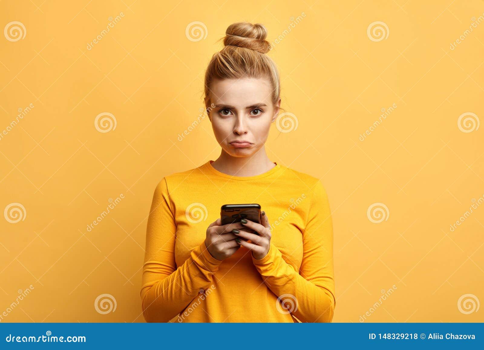 λυπημένη γυναίκα που ενοχλείται από κάτι χρησιμοποιώντας το τηλέφωνοη
