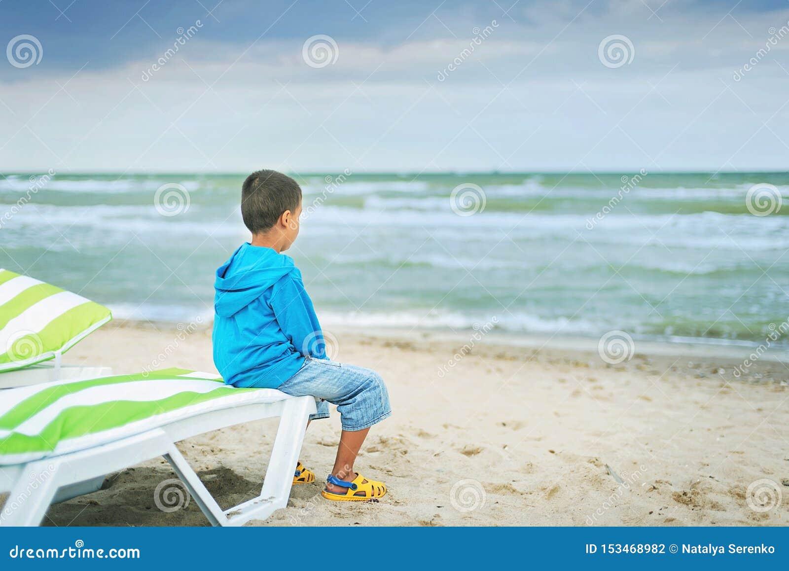 Λυπημένη μόνη συνεδρίαση παιδιών στην παραλία, που φαίνεται εν πλω και που σκέφτεται Το τέλος του καλοκαιριού θλίψη για το τέλος