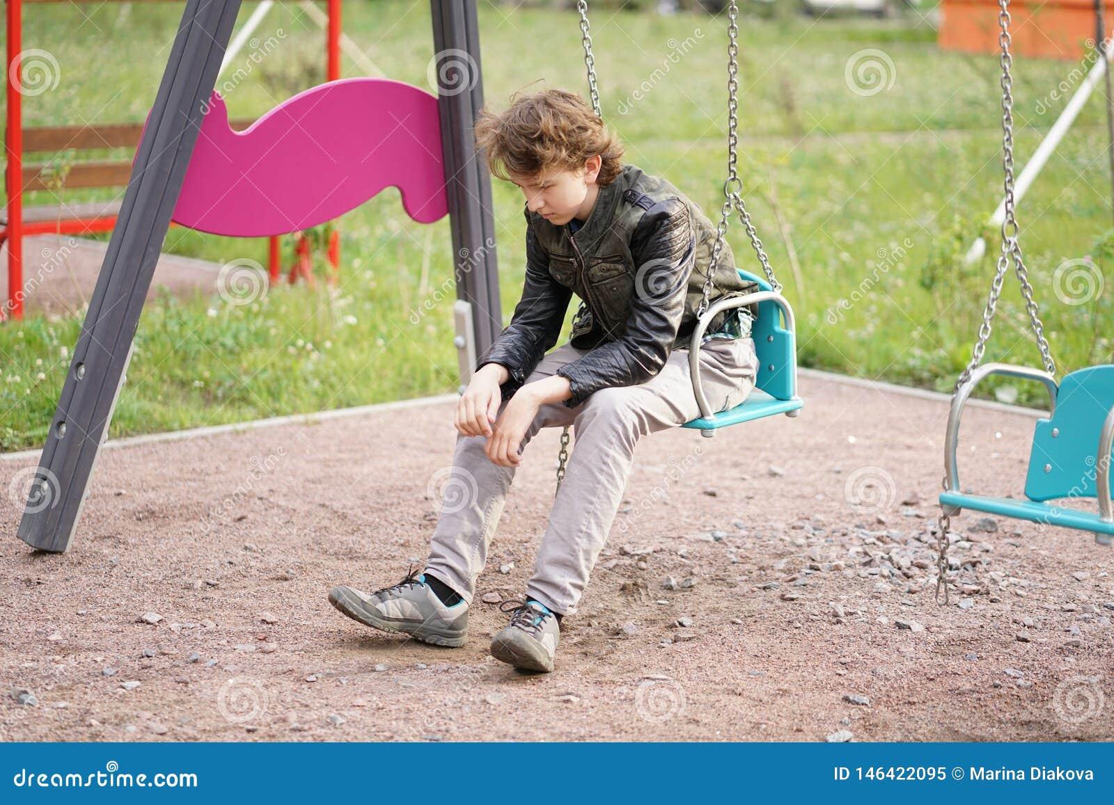 Λυπημένος μόνος έφηβος υπαίθριος στην παιδική χαρά οι δυσκολίες της εφηβείας στην έννοια επικοινωνίας