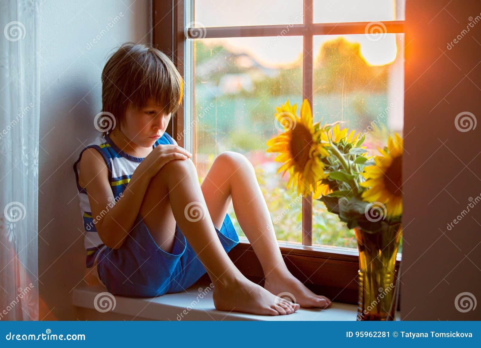 Λυπημένος χαριτωμένος λίγο παιδί μικρών παιδιών, που κάθεται σε ένα παράθυρο, που παίζει με