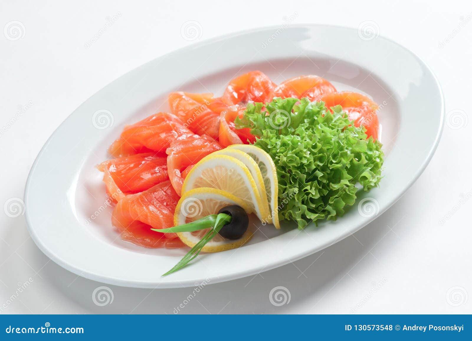 Λωρίδα των κόκκινων ψαριών σε ένα πιάτο με τα πράσινα και το λεμόνι