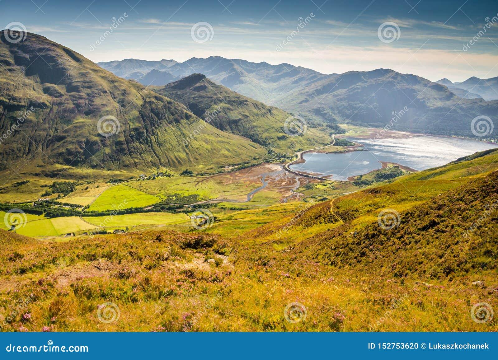 Λόφοι και βουνά κάτω από το όμορφο φως από μέσα από τα σύννεφα και το πράσινο δυτικό Χάιλαντς λόφων στη Σκωτία, που ενώνεται
