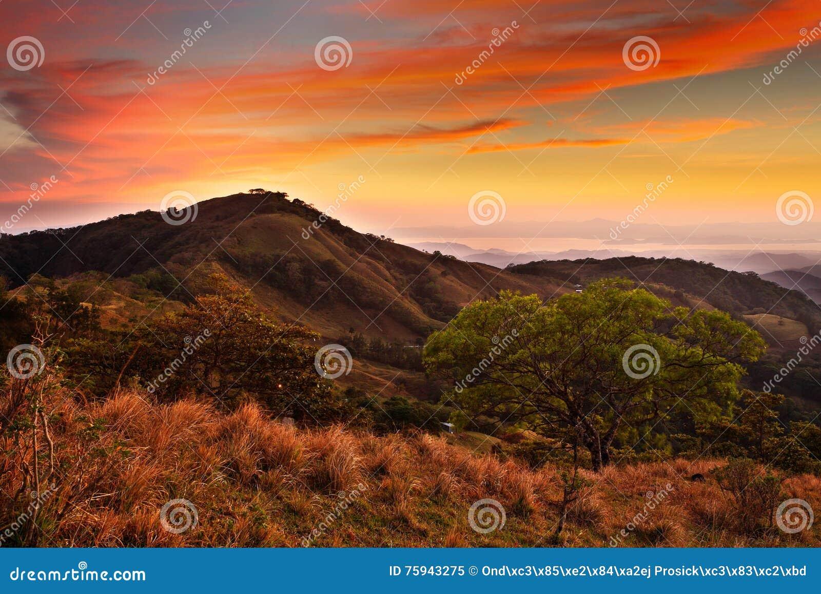 Λόφοι της δασικής επιφύλαξης σύννεφων Monteverde, Κόστα Ρίκα Τροπικά βουνά μετά από το ηλιοβασίλεμα Λόφοι με τον όμορφο πορτοκαλή