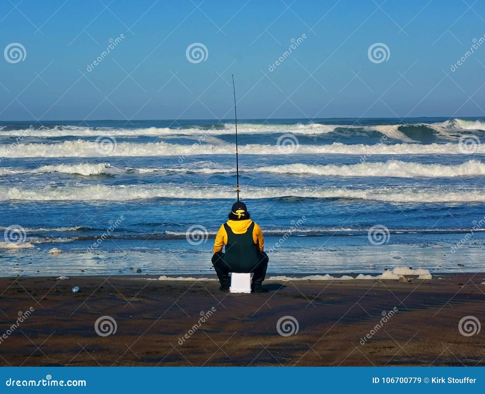 Μάγκα στην ωκεάνια παραλία στο Σαν Φρανσίσκο που κάνει κάποια κυματωγή που αλιεύει καθμένος σε μια άνω πλευρά - κάτω από τον κάδο