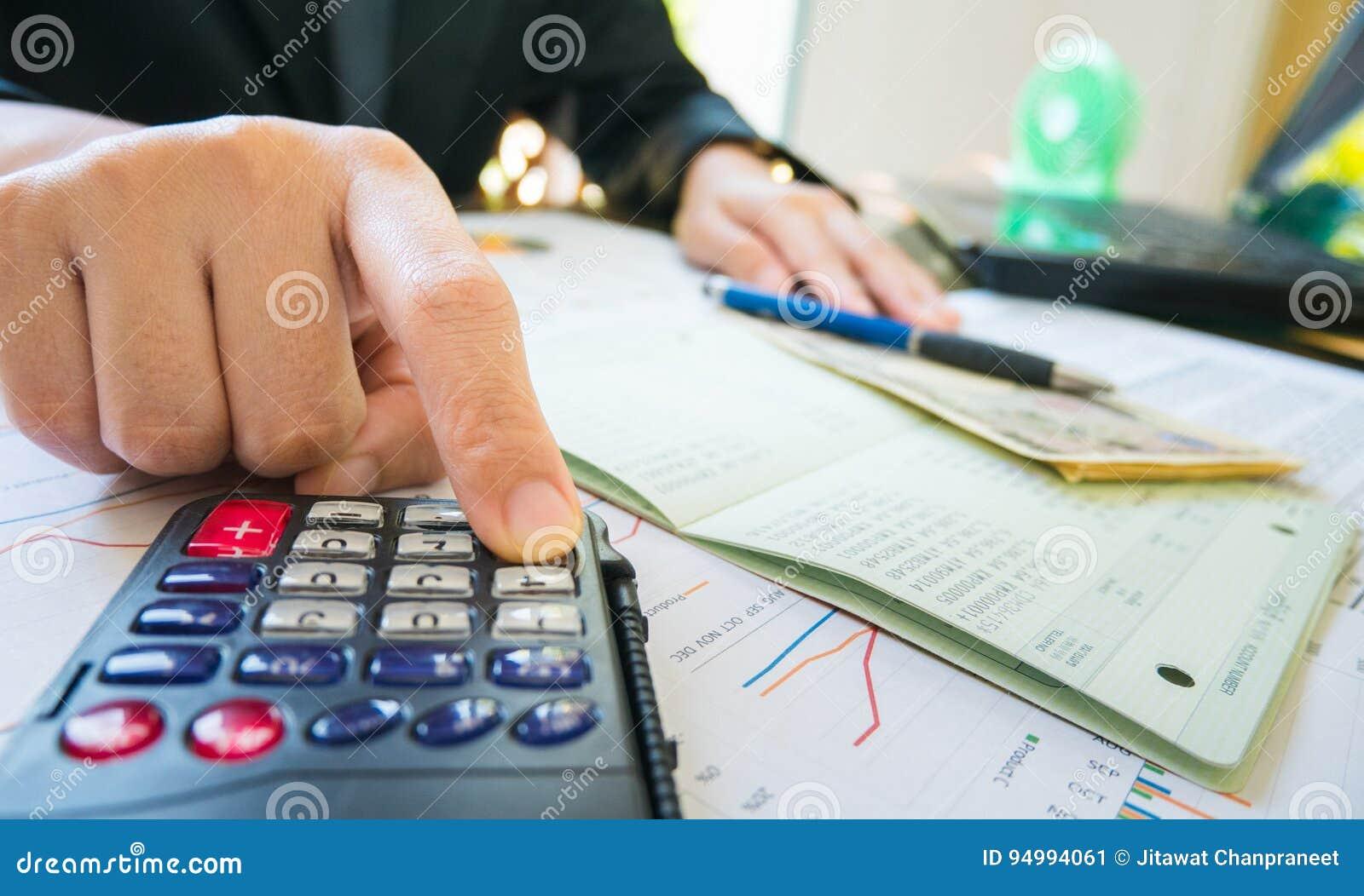 Μάνδρα λαβής χεριών επιχειρησιακών γυναικών και υπολογιστής χρήσης στη δήλωση ή οικονομική έκθεση στην επιχειρησιακή έννοια