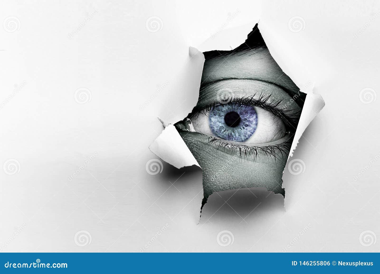 Μάτι σε μια τρύπα του σχισμένου εγγράφου