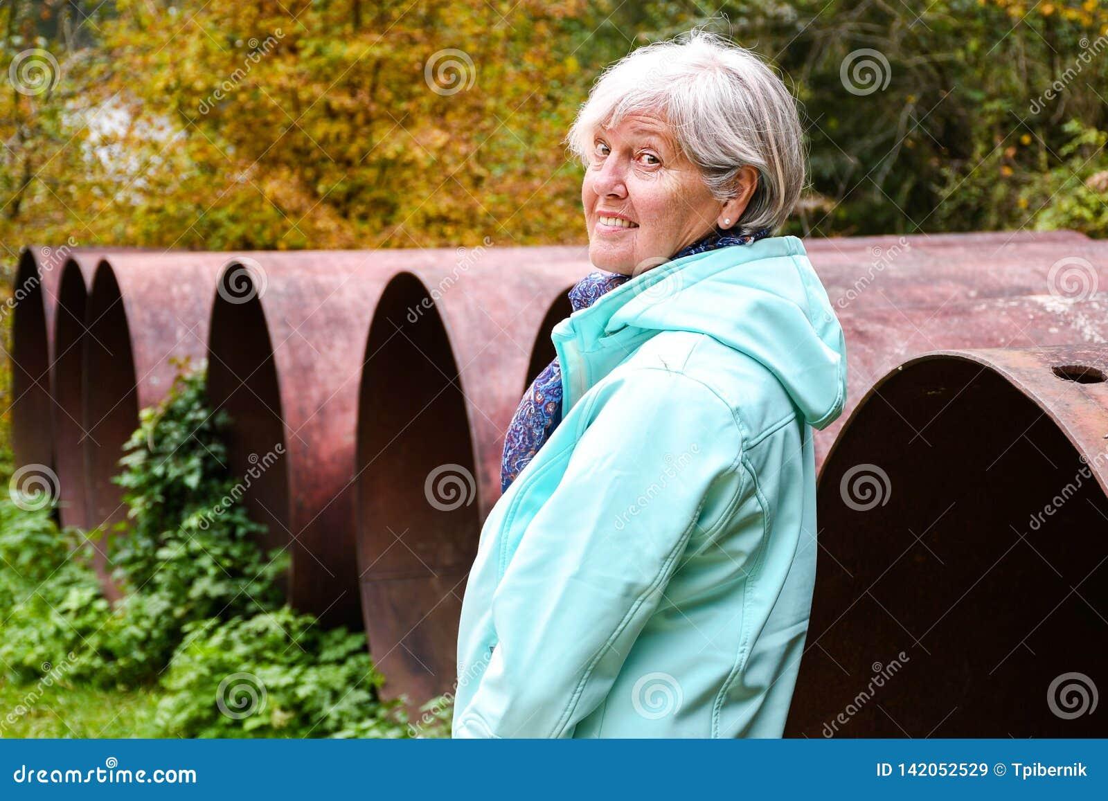 Μέση ηλικίας γυναίκα που στέκεται υπαίθρια το φθινόπωρο κοντά στους μεγάλους παλαιούς σωλήνες κατασκευής γεύματος