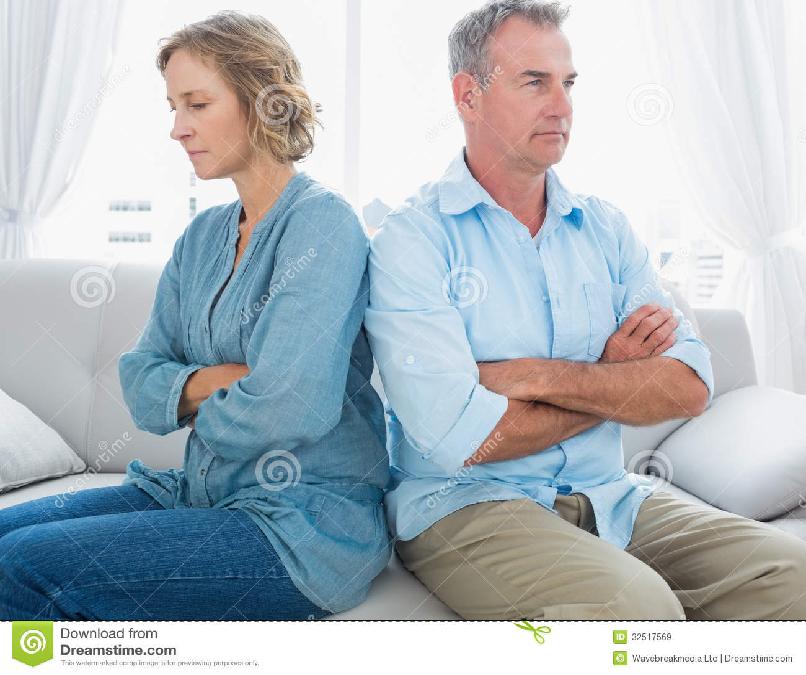 Μέση ηλικίας συνεδρίαση ζευγών στον καναπέ που δεν μιλά μετά από ένα σύκο